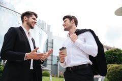 2 жизнерадостных молодых бизнесмена выпивая кофе outdoors Стоковые Изображения