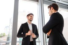 2 жизнерадостных молодых бизнесмена говоря в офисе Стоковые Фото