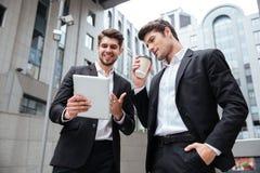 2 жизнерадостных молодых бизнесмена говоря и используя таблетку Стоковое фото RF