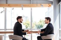 2 жизнерадостных молодых бизнесмена имея деловую встречу Стоковая Фотография