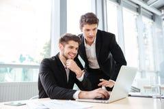 2 жизнерадостных молодых бизнесмена используя компьтер-книжку на деловой встрече совместно Стоковые Фотографии RF