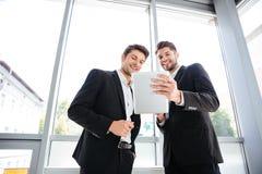 2 жизнерадостных молодых бизнесмена используя таблетку в офисе совместно Стоковая Фотография RF