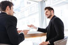 2 жизнерадостных молодых бизнесмена используя таблетку на деловой встрече Стоковое Изображение RF