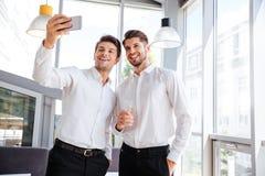 2 жизнерадостных молодых бизнесмена принимая selfie в офисе Стоковые Фото