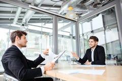 2 жизнерадостных молодых бизнесмена создавая бизнес-план на встрече Стоковые Фотографии RF