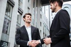 2 жизнерадостных молодых бизнесмена тряся руки Стоковая Фотография RF