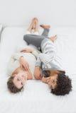 2 жизнерадостных молодых женских друз лежа в кровати Стоковые Фотографии RF