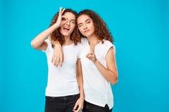 2 жизнерадостных молодых милых девушки дублируют представлять над голубой предпосылкой Стоковое Изображение RF