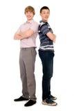 2 жизнерадостных молодых студента стоя спина к спине. Стоковые Фото