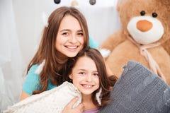 2 жизнерадостных очаровательных сестры играя с подушками Стоковое Фото
