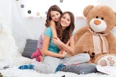 2 жизнерадостных очаровательных сестры сидя в комнате детей Стоковая Фотография RF