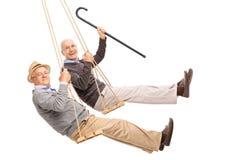 2 жизнерадостных пожилых люд отбрасывая на деревянных качаниях Стоковые Изображения RF