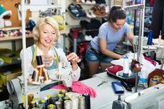 2 жизнерадостных портноя женщин работая с швейными машинами Стоковые Фото