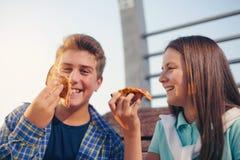 2 жизнерадостных подростка, девушка и мальчик, есть пиццу внешнюю Стоковое Изображение