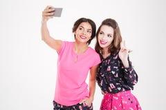 2 жизнерадостных привлекательных женщины стоя и принимая selfie с smartphone Стоковые Изображения
