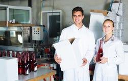 2 жизнерадостных работника стоя в упаковывая разделе на человеке вина Стоковое Изображение