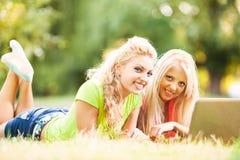 2 жизнерадостных друз с компьтер-книжкой в парке Стоковая Фотография RF