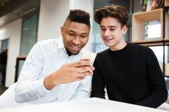 2 жизнерадостных студента в библиотеке используя мобильный телефон Стоковые Фото