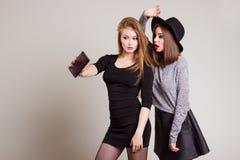 2 жизнерадостных счастливых подруги девушки сфотографировали на телефоне, телефоне собственной личности Стоковая Фотография