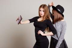 2 жизнерадостных счастливых подруги девушки сфотографировали на телефоне, телефоне собственной личности Стоковое фото RF