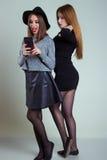 2 жизнерадостных усмехаясь сексуальных подруги девушки сфотографированной на телефоне, делают телефон selfie в студии на серой пр Стоковое фото RF