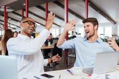 2 жизнерадостных люд давая максимум 5 и работая в офисе Стоковое Изображение