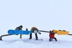 3 жизнерадостных snowboarders повиснули на рельсе для фокусов Стоковые Изображения