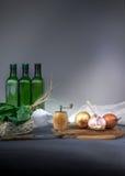 1 жизнь все еще бутылка, лук, чеснок, шпинат, мельница руки, перец на голубой скатерти Космос для текста Стоковое Изображение