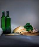 1 жизнь все еще бутылка, хлеб, чеснок, шпинат на голубой скатерти Космос для текста Стоковое Изображение RF