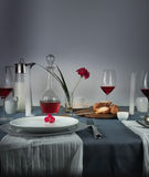 1 жизнь все еще кувшин молока, розового вина в стеклах, плюшки, белых свечей на голубой скатерти Стоковое Фото