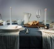 1 жизнь все еще кувшин, стекла, плюшка, белые свечи на голубой скатерти Стоковые Фото