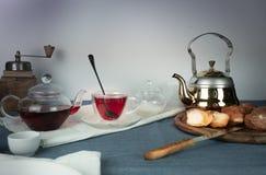 1 жизнь все еще мельница кофе, чай гибискуса, плюшки на голубой скатерти Стоковая Фотография