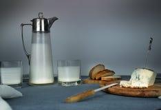 1 жизнь все еще обед деревенский кувшин молока, свечи, чай, яичка, хлеб, крены, сыр, на таблице Стоковые Фотографии RF