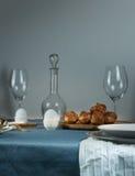1 жизнь все еще обед деревенский старый штоф, стекла, плюшки на таблице с голубой скатертью Стоковое Фото