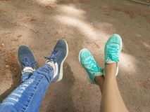 1 жизнь все еще Пересеченный друг с другом 2 пары ног в стилизаторах Одна пара ног в голубых сорванных джинсах и голубых робах с  Стоковые Фотографии RF
