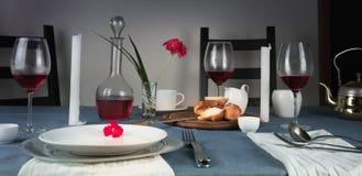 1 жизнь все еще розовое вино в стеклах, плюшка, белые свечи на голубой скатерти Стоковое фото RF