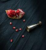 1 жизнь все еще серебряное стекло, отрезанное гранатовое дерево и зерна венисы на темной предпосылке Стоковое Изображение