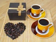 1 жизнь все еще 2 чашки кофе, коробка с подарком и сердце сделанное от кофейных зерен стоковое изображение