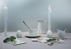 1 жизнь все еще шикарная таблица установки скатерть, свечи, античный фарфор - чашка, поддонник, яичка Стоковое фото RF