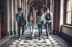 Жизнь коллежа Группа в составе студенты идет в залу и беседовать университета стоковое фото