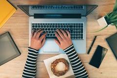 Жизнь офиса, женские руки работая на портативном компьютере, взгляд сверху Стоковое Фото