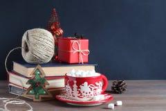 жизнь рождества все еще Кружка рождества с зефирами, куча книг и красный подарок Стоковая Фотография