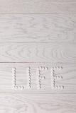 Жизнь слова сделанная пилюлек на таблице Стоковые Фото