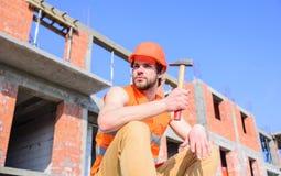 Жилет построителя и строительная площадка шлема сидят ослаблять Шлем Гая защитный сидит перед зданием сделанным из стоковая фотография rf