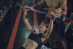 Жим лежа женщины личного тренера помогая в спортзале, тренировке со штангой, личной женщиной порции тренера работая с гантелями стоковая фотография