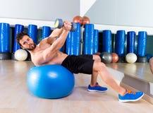 Жим лёжа гантели на разминке человека шарика пригонки на спортзале Стоковая Фотография