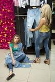 2 джинса покупки девушек в магазине утомленная подруга Стоковое Изображение