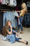 2 джинса покупки девушек в магазине утомленная подруга Стоковые Изображения