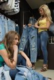 2 джинса покупки девушек в магазине утомленная подруга Стоковые Изображения RF