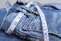 джинсыы измеряя ленту стоковые фото